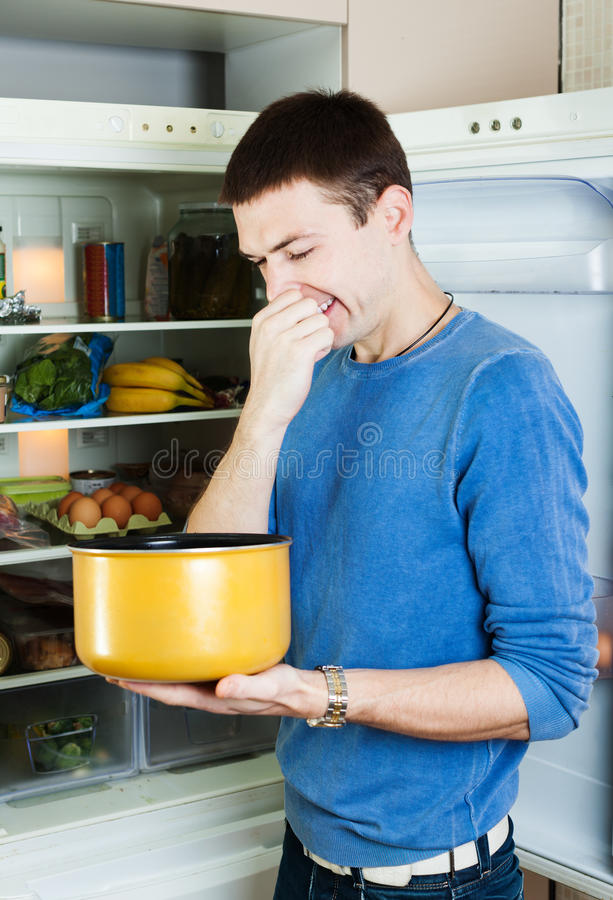 Man holding her nose because of bad smell from food royalty free stock images
