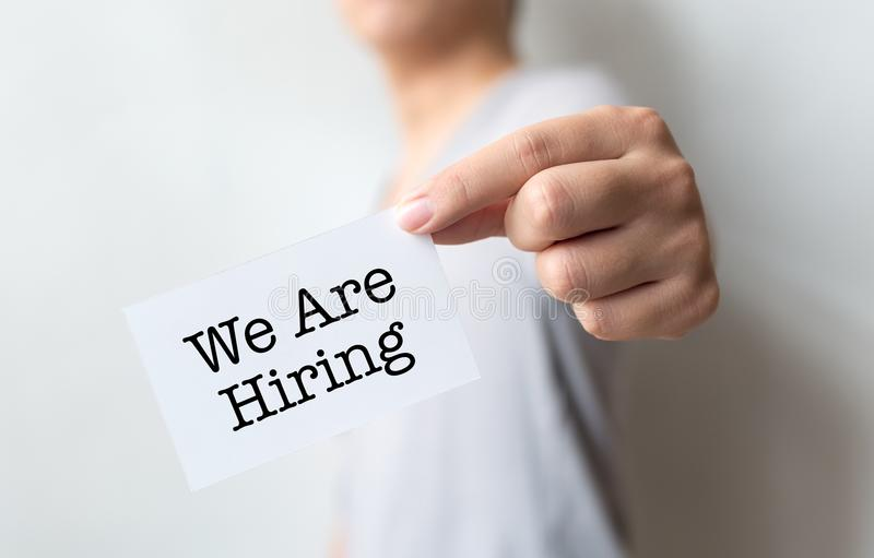 Man holding we are hiring word on paper card, Concept job recruitment and human resource stock photos