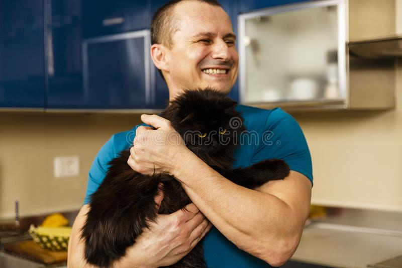 a man holding his adorable furry black cat stock images