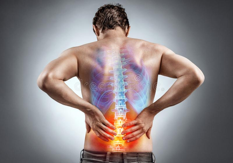 Man holding his back in pain. Lower back pain. Man holding his back in pain. Medical concept