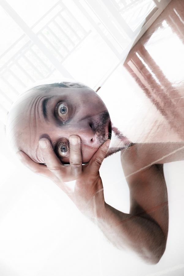 Man holding his head in his hand, tired out by the complexity of life, heavy head, burn out. Man suffering from mental disorder royalty free stock photography