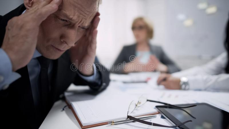 Man holding his head, migraine attack caused by stress, exhaustion at workplace. Stock photo stock photos