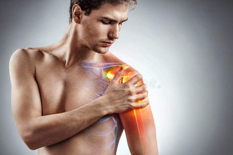 Man holding his injured shoulder that`s highlighted in red. Medical concept stock photos
