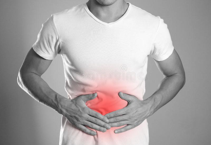 The man is holding his stomach. Abdominal pain. The hearth is hi stock photography