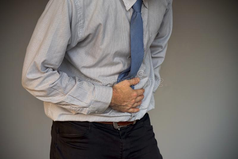 Businessman suffering from abdominal pain. Man holding his stomach in pain isolated on gray background. Businessman suffering from abdominal pain. Body And stock photo