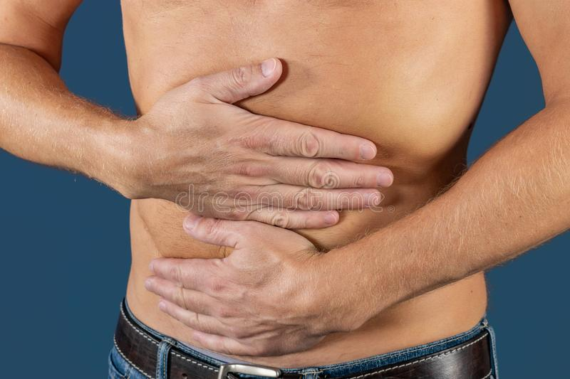 Man holding his stomach in pain. Man with naked torso experience stomachaches on blue background. Medical concept stock images