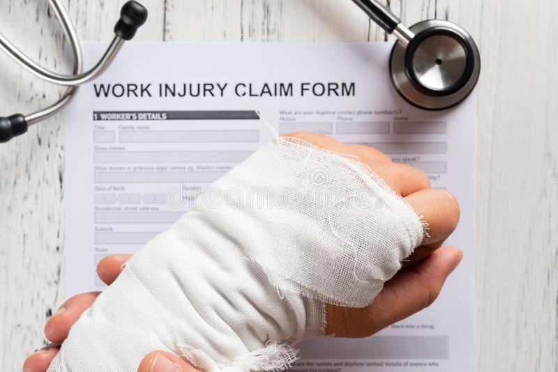 Man holding his wrapped hand on top of a work injury claim form with stethoscope medical & insurance concept. Man holding his wrapped hand on top of a work stock image