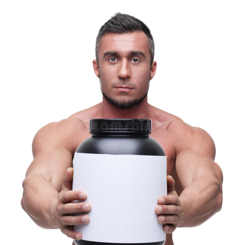 Man holding holding jar with protein. Serious muscular man holding holding jar with protein stock photos