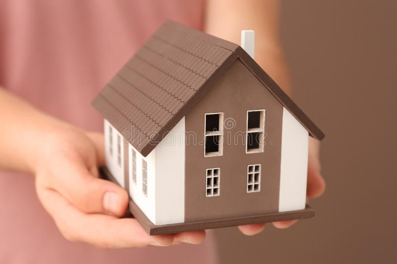 Man holding house model on color background, closeup. Mortgage concept stock photo