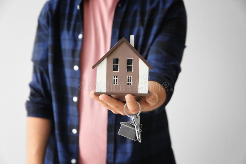 Man holding house model and key on light background, closeup. Mortgage concept stock photography