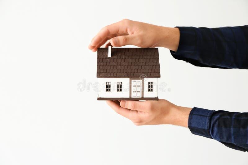 Man holding house model on light background stock image