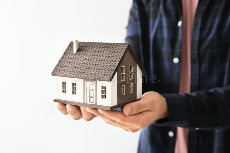 Man holding house model on light background, closeup. Mortgage concept stock photography