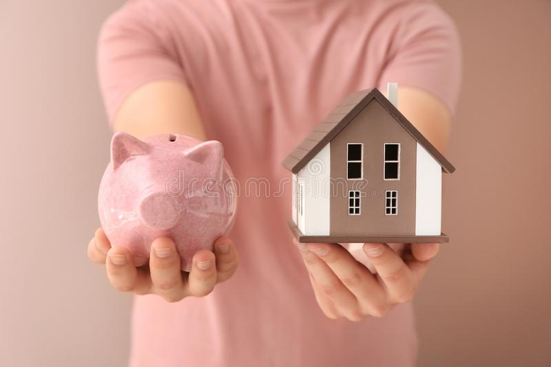 Man holding house model and piggy bank on color background. Mortgage concept royalty free stock photos