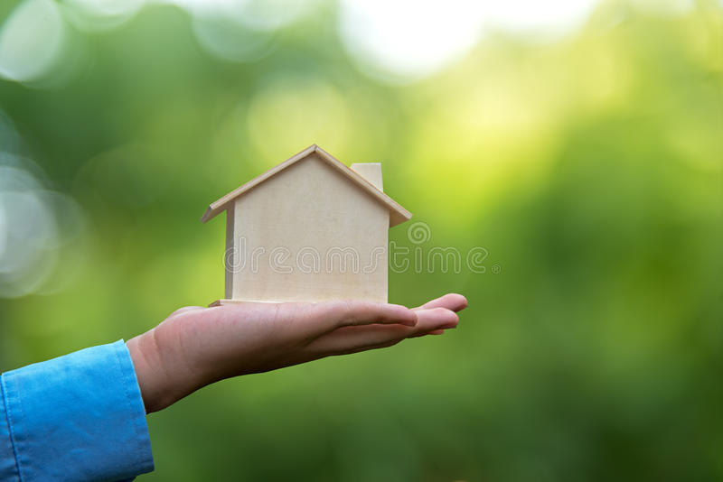 Man holding house representing home ownership and saving money. The Real Estate business stock images