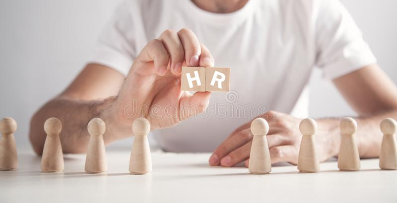 Man holding HR word on wooden cubes. Human Resources royalty free stock image