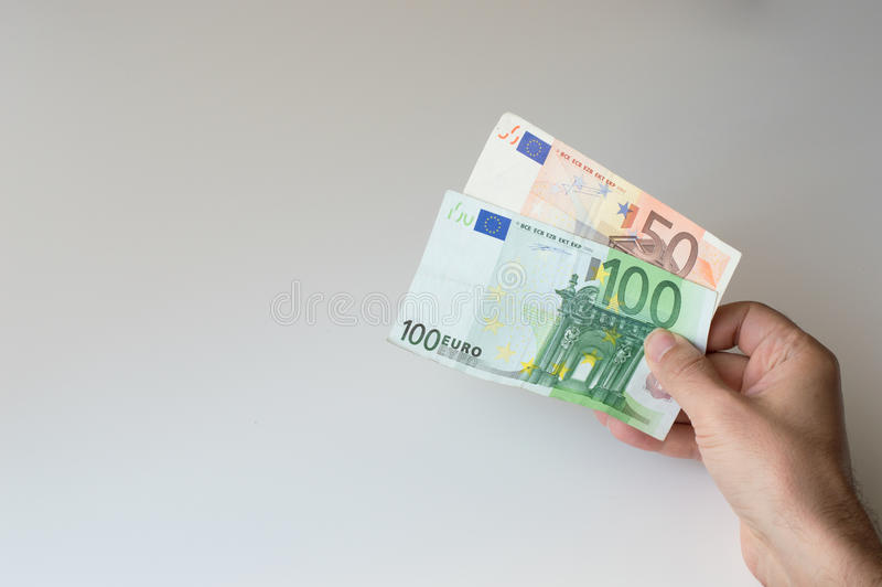 Man holding a hundred and fifty Euro banknote. In his hands stock photography