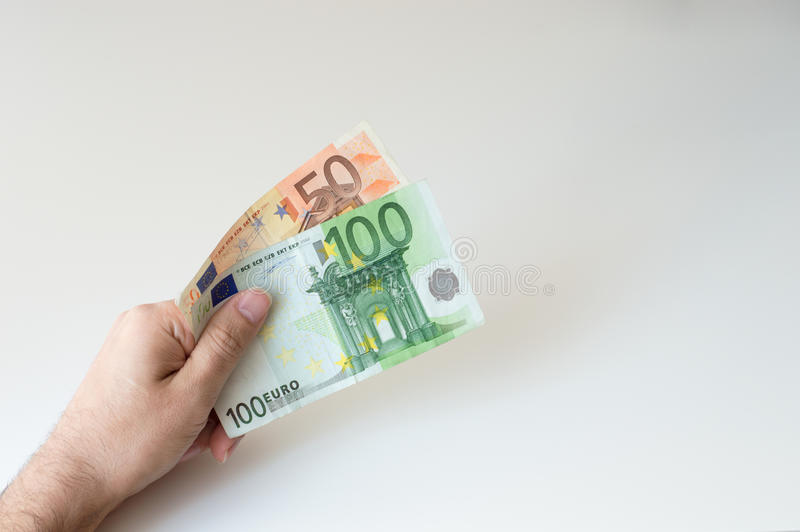 Man holding a hundred and fifty Euro banknote. In his hands stock images