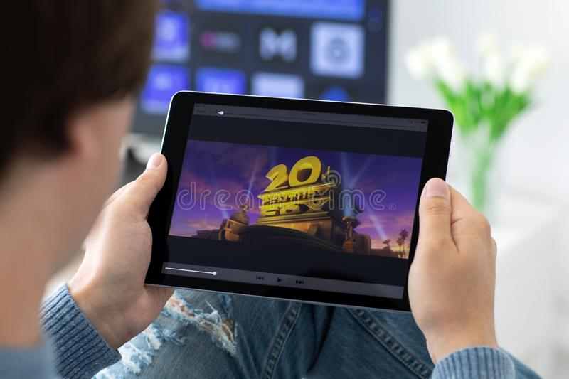 Man holding iPad with movie 20 century on the screen royalty free stock photo