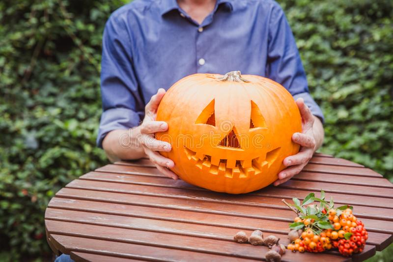 A man holding a jack o lantern carved halloween pumpkin on the wooden table. Happy Halloween stock photos