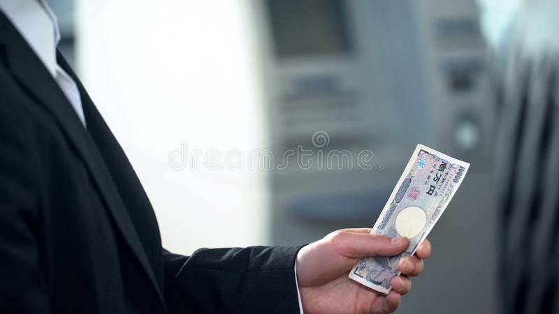 Man holding Japanese Yen banknotes withdrawn from ATM, good service, travelling royalty free stock photos