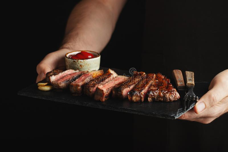 Man holding juicy grilled beef steak with spices and red sauce on a stone cutting board on a black background royalty free stock photography