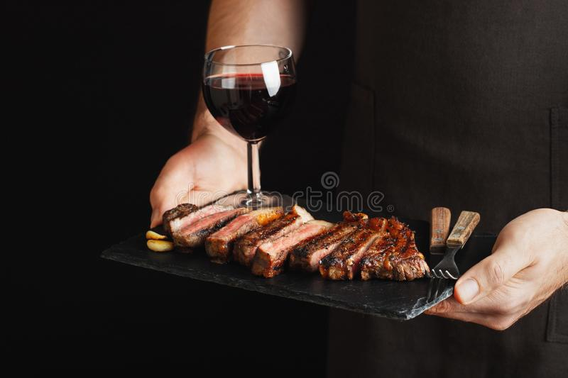 Man holding juicy grilled beef steak with spices and red wine glass on a stone cutting board on a black background. With stock photo