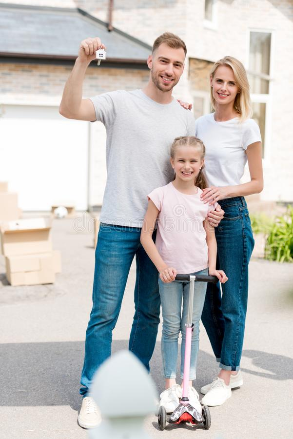 man holding key with trinket while his wife embracing daughter on kick scooter in front of new royalty free stock photography
