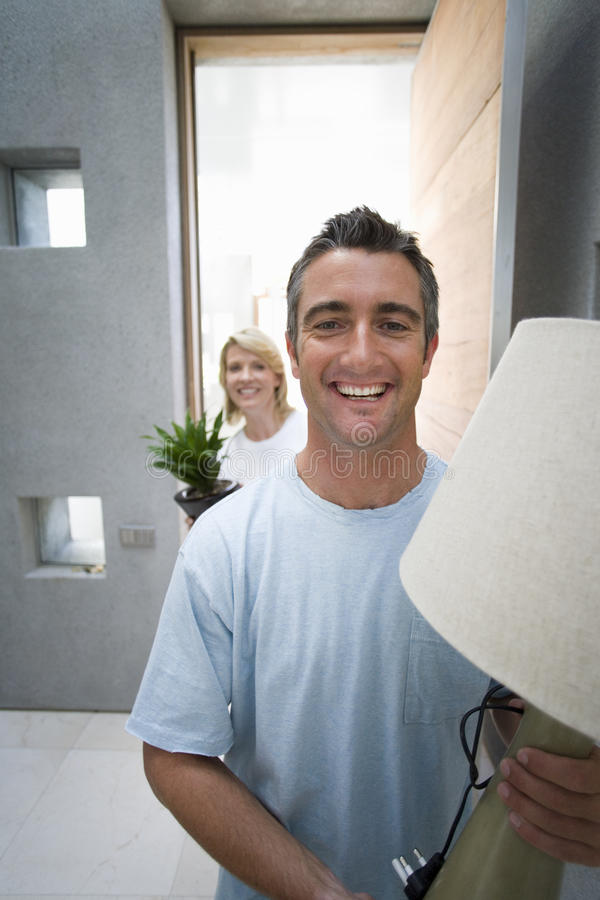 Man holding lamp, woman holding pot plant, smiling, portrait royalty free stock image