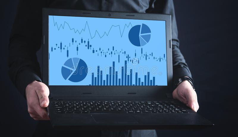 Man holding laptop with graphs in screen stock images