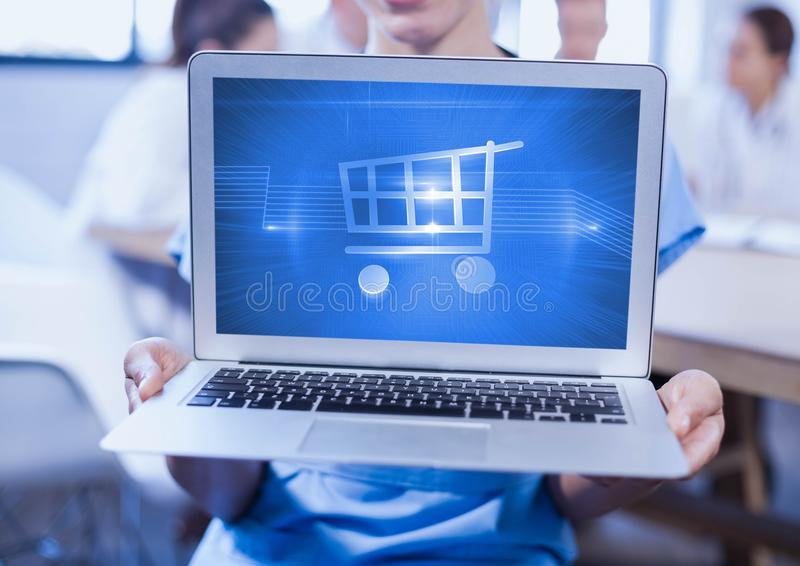 Man holding a laptop showing shopping cart on screen. Against blur background royalty free stock photography