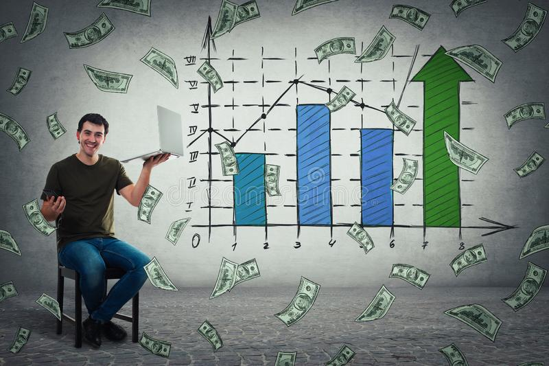Man holding laptop and smartphone celebrate business success, showing a positive increasing graph of virtual sales and money. Young man sitting on chair holding royalty free stock images