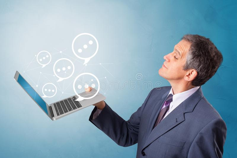Man holding laptop with speech bubbles. Man holding laptop with a few speech bubble symbols royalty free stock images