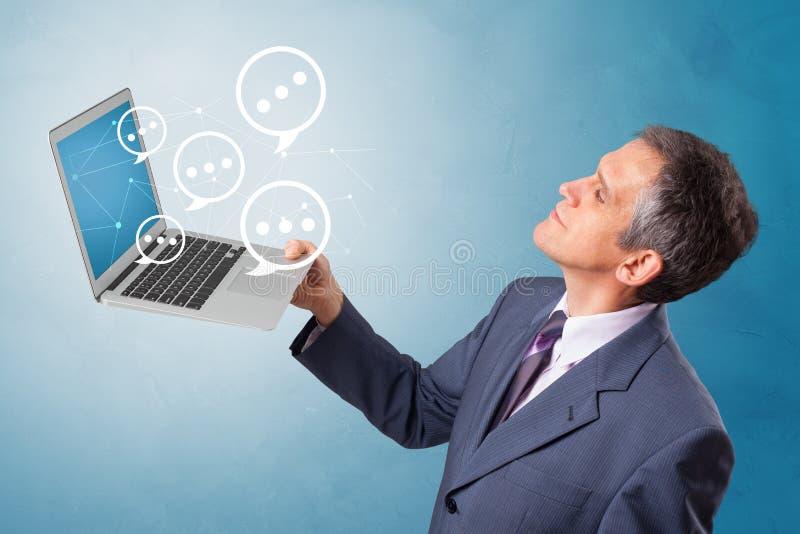 Man holding laptop with speech bubbles. Man holding laptop with a few speech bubble symbols stock photos