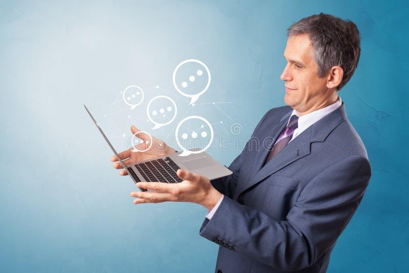 Man holding laptop with speech bubbles. Man holding laptop with a few speech bubble symbols royalty free stock photo