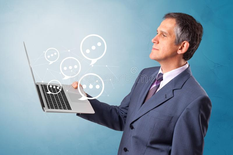 Man holding laptop with speech bubbles. Man holding laptop with a few speech bubble symbols stock photography