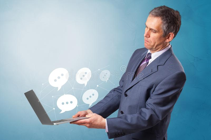 Man holding laptop with speech bubbles. Man holding laptop with a few speech bubble symbolsn stock images