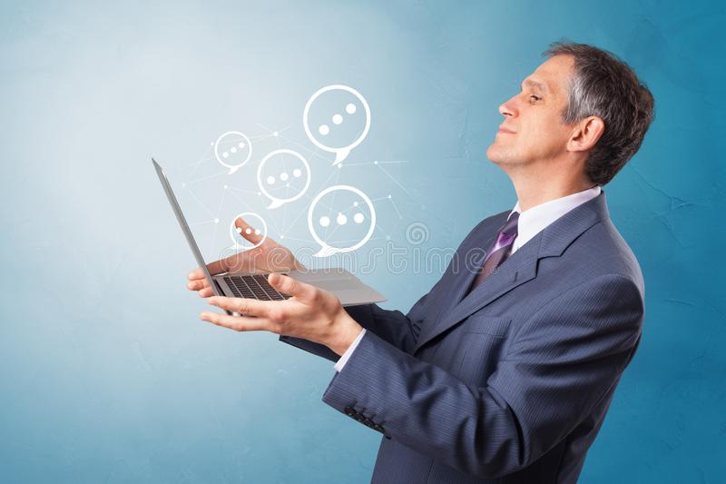 Man holding laptop with speech bubbles. Man holding laptop with a few speech bubble symbols royalty free stock photography