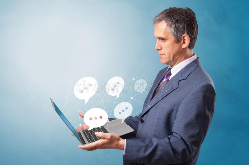 Man holding laptop with speech bubbles. Man holding laptop with a few speech bubble symbolsn royalty free stock photography