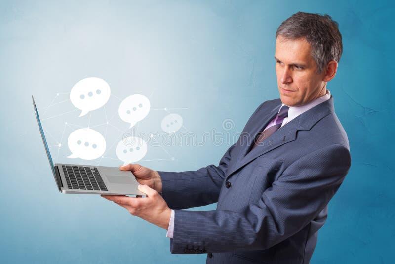 Man holding laptop with speech bubbles. Man holding laptop with a few speech bubble symbolsn royalty free stock photos