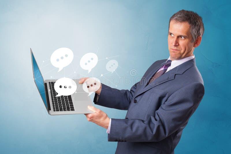 Man holding laptop with speech bubbles. Man holding laptop with a few speech bubble symbols stock photo