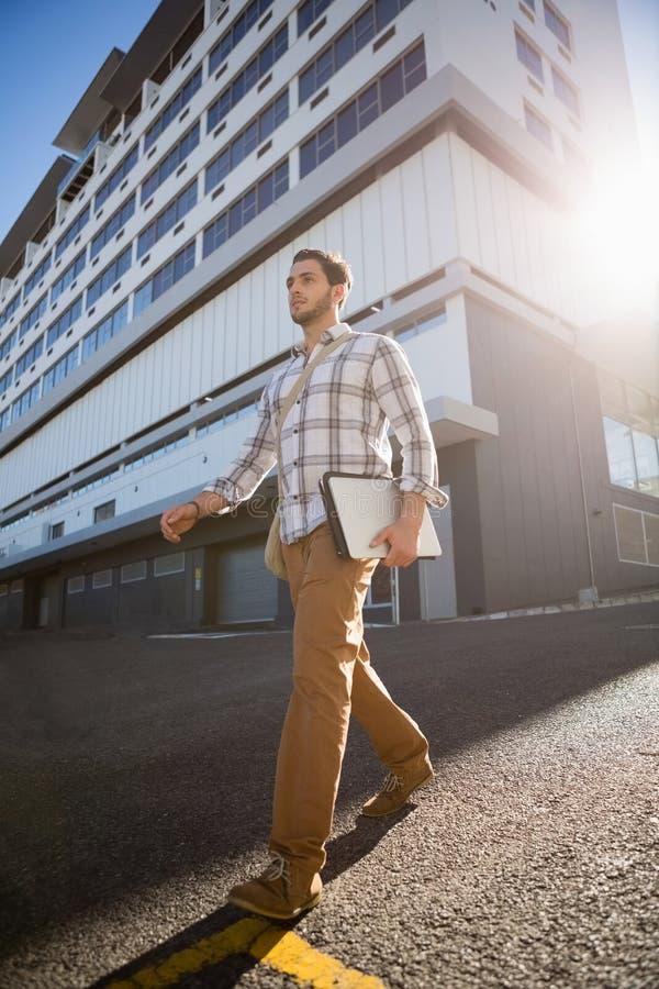 Man holding laptop while walking on city street. Low angle view of man holding laptop while walking on city street royalty free stock image