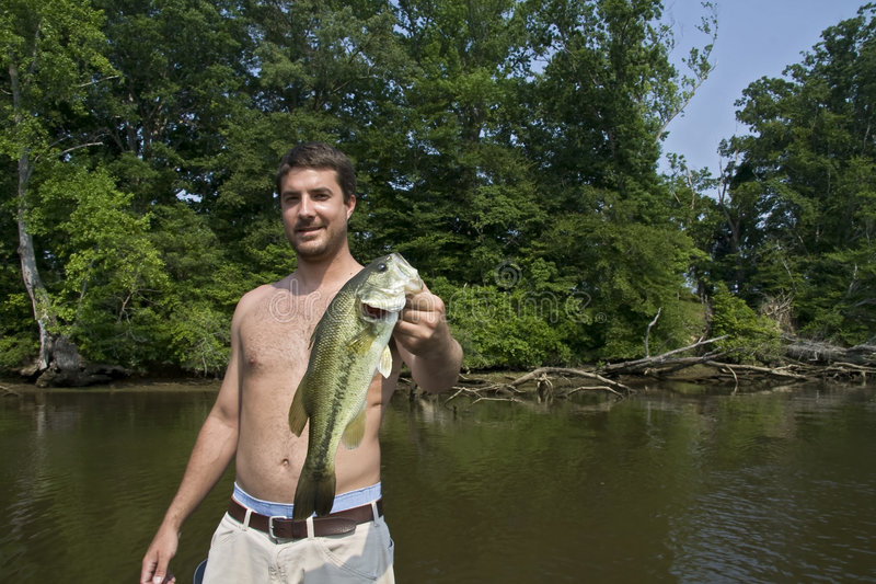 Man holding large mouth bass. Young man happy after catching a big large mouth bass out of a river stock images