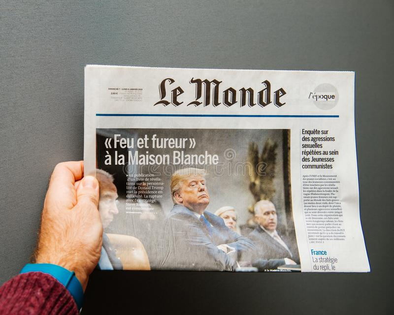 Man holding Le Monde Newspaper with Donald Trump. Paris, France - Jan 8, 2018: Man holding Le Monde Newspaper with Donald Trump and title fire and fury at the royalty free stock images