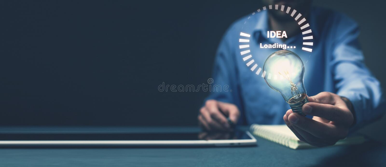 Man holding light bulb. Idea loading stock photo