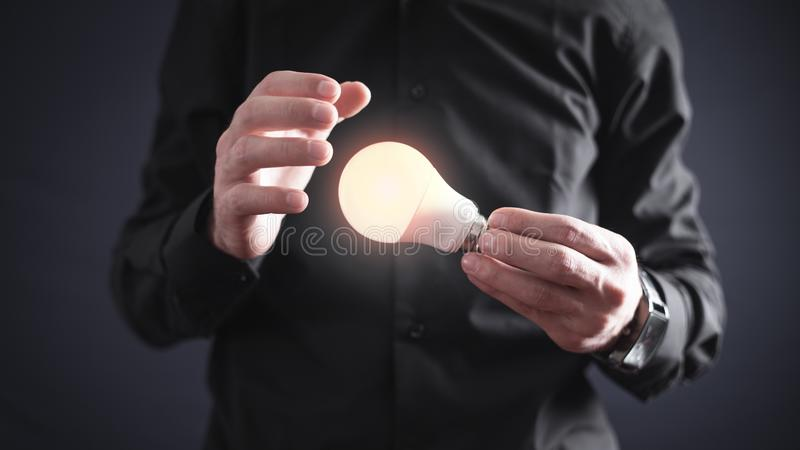 Man holding light bulb. Inspiration and creativity stock photography