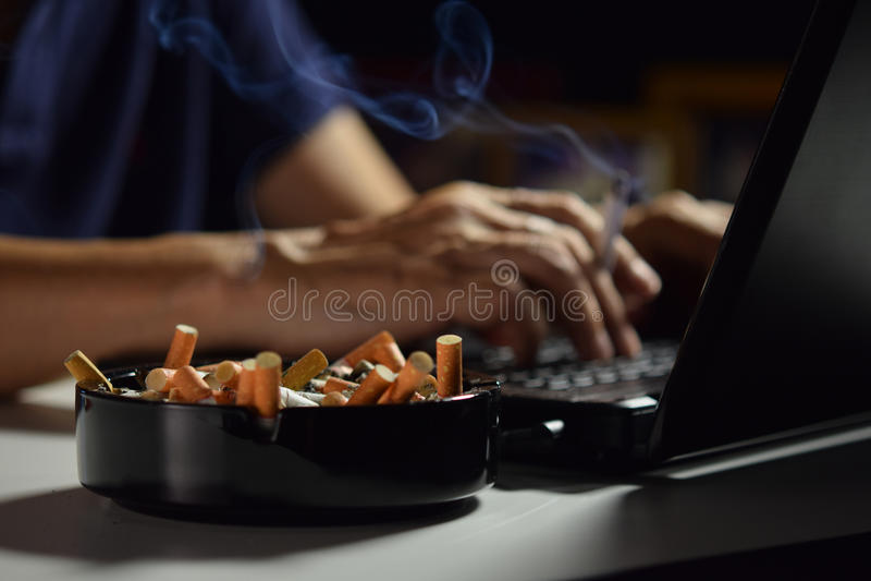 Man holding lit and smoking cigarette stock image