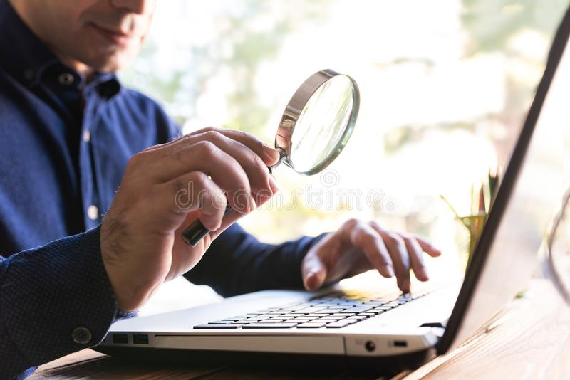 Man Holding a Magnifying Glass, Searching On Internet royalty free stock images