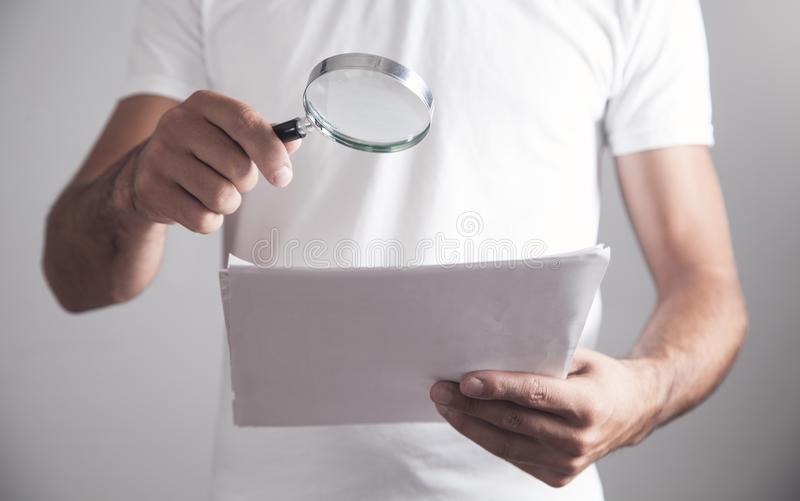 Man holding magnifying glass with documents royalty free stock photo