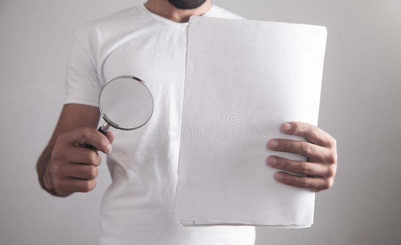 Man holding magnifying glass with documents royalty free stock image