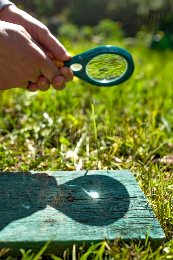 Man holding a magnifying glass making fire, focused on wood. Man holding a magnifying glass making fire, focused on wood on summer day stock photo